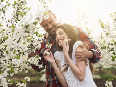 Young, heterosexual couple enjoying among trees in bloom.