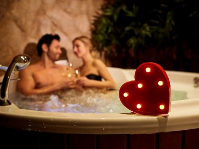 Heart on a background of a romantic couple with champagne in the a hot tub