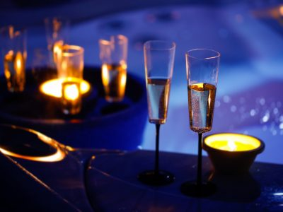 Extravagant, private romantic candlelit champagne glasses with a jacuzzi in the background. Love, celebration, relax, romance, luxurious vacation, wellness spa concept.